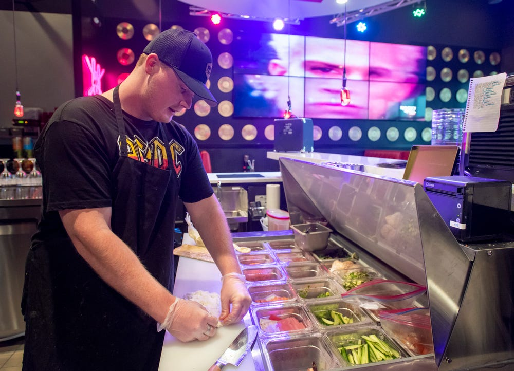 Sushi chef Peter Reisterer III prepares a Metalhead Roll at the new Rock n Roll Sushi restaurant at the Nine Mile Crossing shopping plaza in Beulah on Friday, July 2, 2021.
